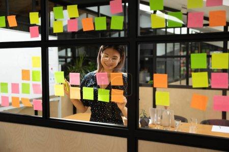 Photo pour Sourire asiatique femme chef de projet dans l'organisation des lunettes processus de travail au panneau de kanban fenêtre en verre. Heureux employé vietnamien ajouter des autocollants en papier avec des tâches, améliorer la gestion des idées au bureau . - image libre de droit