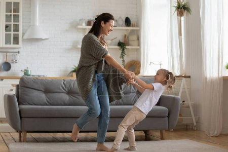 Photo for Overjoyed energetic small adorable daughter twisting with young mother. Happy 30s woman dancing to music with laughing little preschool daughter on carpet at studio kitchen, full body length image. - Royalty Free Image
