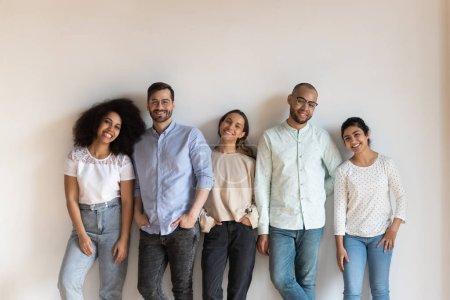 Foto de Raza mixta sonriente jóvenes amistosos de pie cerca de la pared blanca, retrato. Grupo de estudiantes multirraciales felices posando para la foto en la reunión. Exitosos colegas diversos equipo mirando a la cámara . - Imagen libre de derechos