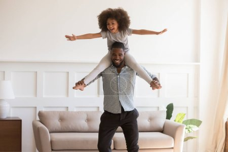 Photo for Loving african American young dad carry preschooler mixed race daughter on shoulder play at home together, happy biracial father and girl child have fun entertain in living room on weekend - Royalty Free Image