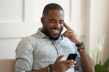 Photo for Smiling african American millennial man sit on couch at home texting messaging on smartphone, happy biracial young male relax use cellphone, browse internet, chat having pleasant conversation - Royalty Free Image