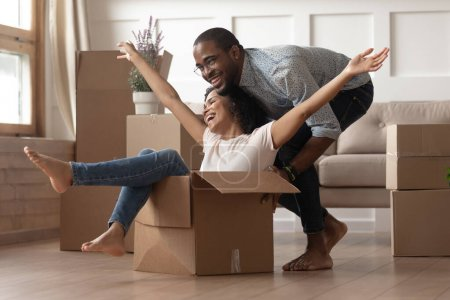 African happy wife sitting inside carton box husband rides her