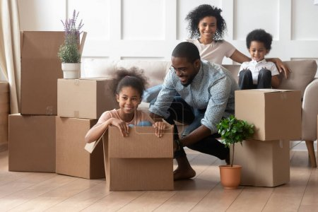 Photo for Overjoyed african family enjoy relocation day at new modern house, father push daughter sitting inside of carton box having fun riding in cozy living room, loan mortgage, housing improvement concept - Royalty Free Image