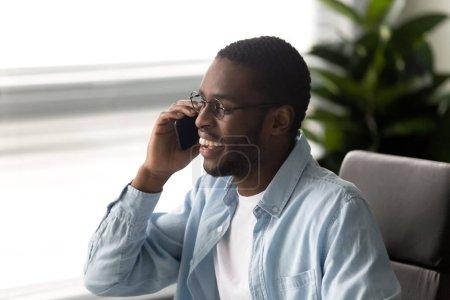 Photo pour Un homme africain souriant d'un millénaire américain en lunettes parlant sur un téléphone cellulaire ayant une conversation agréable, un jeune homme d'origine biracienne heureux parlant sur un téléphone intelligent faisant des appels amicaux à l'aide d'un appareil mobile moderne - image libre de droit