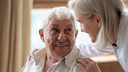 Photo for Head shot close up cheerful elderly man looking at pleasant middle aged nurse. Mature female doctor embracing shoulders, communicating with smiling 80s patient, giving support and psychological help. - Royalty Free Image