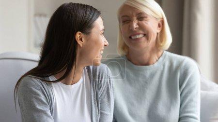 Photo pour Concentrez-vous sur la fille adulte gaie parlant avec des femmes mères âgées ayant agréable conversation drôle assis sur le canapé intérieur, la compréhension et la bonne relation entre la mère âgée et l'enfant adulte concept - image libre de droit