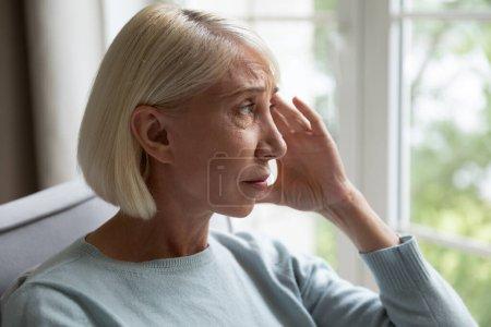 Photo pour Gros plan 50 ans femme assise à l'intérieur regarder par la fenêtre et la pensée, perdu dans des pensées tristes se sent inquiet de la vie personnelle ou des problèmes de santé, souffre de migraine, passe par le concept de divorce - image libre de droit