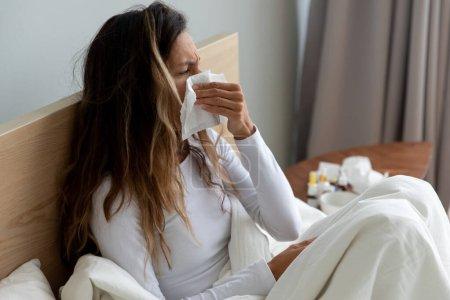 Photo pour Malade femme biraciale des années 30 assis sur le lit, recouvert d'une couverture blanche éternuement tenant mouchoir en papier, essuyant le nez qui coule, se sent malsain souffrant de grippe saisonnière, attrapé un concept froid - image libre de droit