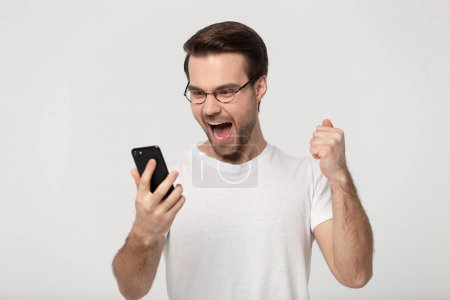 Photo pour Overjoyed young Caucasian man wearing glasses isolated on grey studio background scream winning online lottery or game on cellphone, excited millennial guy shout get amazing good news on cell - image libre de droit