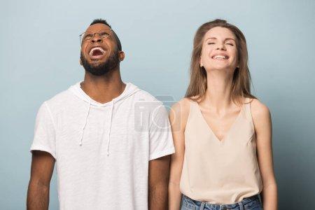 Photo pour Un couple heureux et diversifié riait d'une plaisanterie hilarante ensemble, excitait un Afro-Américain en lunettes et une Caucasienne en s'amusant, riait en éclats, se tenait isolé en studio - image libre de droit