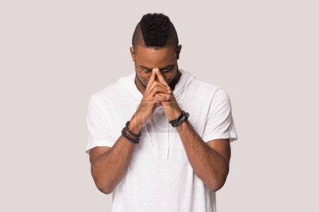Photo pour Jeune homme afro-américain concentré dans des lunettes priant avec espoir, méditant, homme calme réfléchi tenant la main dans la prière, pensant au problème, isolé sur fond de studio gris - image libre de droit