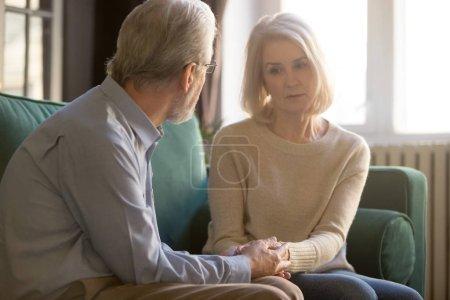 Photo pour Soixante ans conjoints assis sur le canapé, mari âgé aimant réconfortant femme triste frustrée, couple stationnaire tient la main l'homme fait preuve d'amour, de soins et d'empathie, montrant concept de soutien femme bien-aimée - image libre de droit