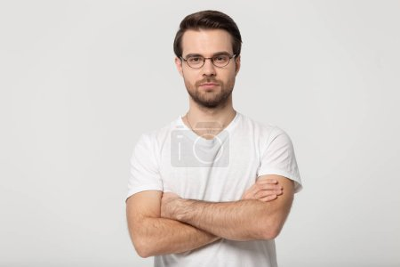 Serious millennial man in glasses posing with arms crossed