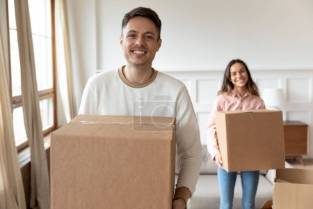 Photo for Happy young man carrying box moving into new house with girlfriend, smiling couple roommates renters tenants packing unpacking relocating removals standing in modern rental apartment new home concept - Royalty Free Image