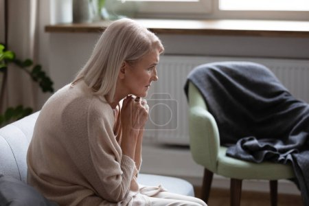 Photo for Middle-aged 50s hunched woman seated on couch at home feels upset thinking. Concept of older generation chronic diseases, widow female goes through death of husband, dementia mental disorder concept - Royalty Free Image