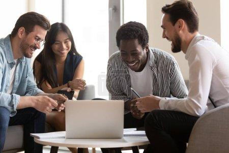 Photo pour Quatre différents collègues ethniques asiatiques caucasiens africains sympathique personnel de l'entreprise assis ensemble dans le salon de bureau sur le canapé regarder vidéo drôle pendant la pause, de bonnes relations et le concept d'amitié - image libre de droit
