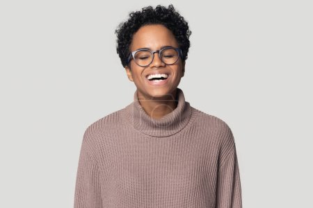 Photo for Excited happy african american young woman in warm sweater feeling joyful, laughing at joke, having fun head shot portrait. Ethnic girl in eyeglasses having fun, isolated on grey studio background. - Royalty Free Image