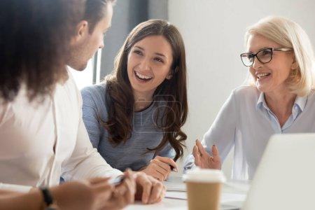 Photo pour Diverses personnes sont assises au bureau parler et rire écouter un collègue parler, les gens d'affaires sourire bavarder lors d'une réunion occasionnelle sur le lieu de travail, les employés s'amusent à discuter du projet d'entreprise ensemble - image libre de droit