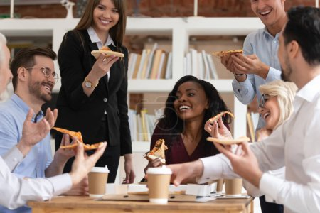 Photo pour Diverse age ethnicity colleagues eat pizza during lunch at workday, multi-ethnic workers enjoy party celebrate successful deal have fun chatting, teambuilding friendship at work, food delivery concept - image libre de droit