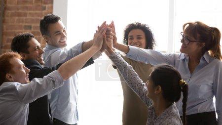 Photo pour Des gens d'affaires multiraciaux ravis réussissent leur but en donnant cinq se sentent excités. Une équipe d'entreprise qui réussit à se féliciter et à remporter la victoire se tient la main montre un esprit d'unité - image libre de droit