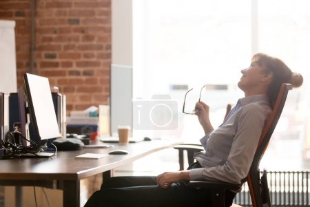 Photo pour Side view relaxed business woman taking off eyeglasses reposing on comfortable chair sitting alone in modern office, take break, dreaming, feel good tranquil after work. Concept de décompression - image libre de droit