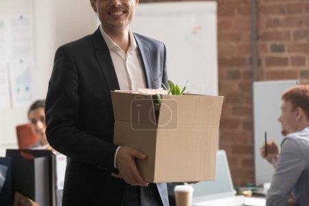 Photo pour Image agrandie nouvel employé en costume officiel debout dans un bureau partagé sourire regarder un membre de l'équipe de caméra tenant une boîte de carton avec des choses en début de carrière dans une entreprise internationale. Principe du premier jour ouvrable - image libre de droit