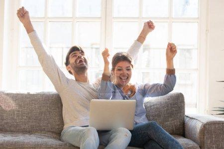 """Photo pour Un jeune couple heureux célèbre la victoire en ligne, criant de joie en levant les mains, regardant ensemble l """"écran d'un ordinateur portable, épouse et mari reçoivent de bonnes nouvelles, accomplissements, nouvelle grande offre, succès - image libre de droit"""
