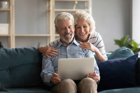Photo pour 60 épouses âgées à la maison épouse câlins mari par derrière alors qu'il est assis sur le canapé faisant vidéocall avoir conversation agréable bavarder avec des enfants adultes petits-enfants en utilisant le concept de technologie sans fil - image libre de droit