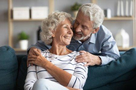 Photo pour Les conjoints âgés qui s'intéressent l'un à l'autre malgré l'ensemble vécu vivent ensemble aiment passer du temps à parler à l'intérieur, aimer mari voyou câlins par derrière jolie femme, mariage heureux et concept d'amour éternel - image libre de droit