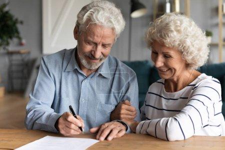 Photo pour 60 ans conjoints âgés au cabinet d'avocat assis au bureau mari stylo tenant famille prêt à signer contrat de mariage faire des formalités juridiques au notaire, léguer des économies et des biens aux enfants concept - image libre de droit