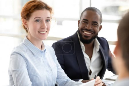 Diverse smiling colleagues listen to coworker talking at meeting