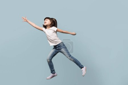 Foto de Muy alegre adorable a lo largo de toda la longitud pequeña y divertida preschool chica saltando a un lado, volando, divertiéndose, jugando, aislado en el fondo de estudio azul, emociones positivas, buen humor juguetón concepto.. - Imagen libre de derechos