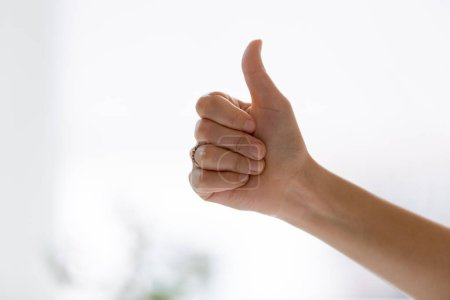 Photo for Close up of female hand showing thumbs up express positive feedback, client recommends services of good, finger up as symbol of successful result, work done, business or personal achievement concept - Royalty Free Image