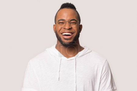 Photo for Excited african American young man in glasses and sport clothes isolated on grey background laugh looking ta camera, smiling black millennial male in casual wear and spectacles feel happy overjoyed - Royalty Free Image
