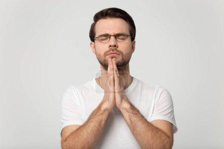 Photo pour Jeune prière concentrée dans les lunettes avec les yeux fermés les mains croisées et espérant tout le meilleur, demandant de la santé, bonne chance, aide. Tête tournée priant homme isolé sur fond gris studio portrait . - image libre de droit
