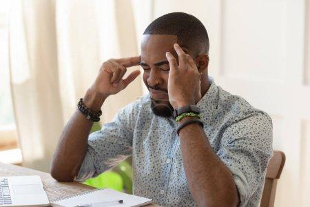 Hombre africano con exceso de trabajo sufre de migraña dolor de cabeza severo