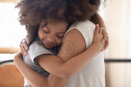 africana hija cerrado ojos acurrucado hasta a madre abrazó su