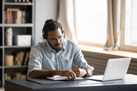 Photo for Concentrated millennial african american guy wearing earphones, listening to favorite music while planning workday. Focused young biracial businessman watching educational lecture. writing down notes. - Royalty Free Image