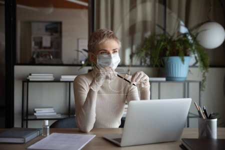 Photo for Distracted from job young thoughtful businesswoman in protective facial mask and gloves sitting at workplace, looking away, thinking of online company strategy development during quarantine time. - Royalty Free Image