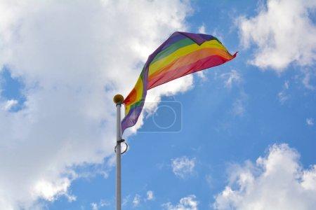 Rainbow flag against blue sky