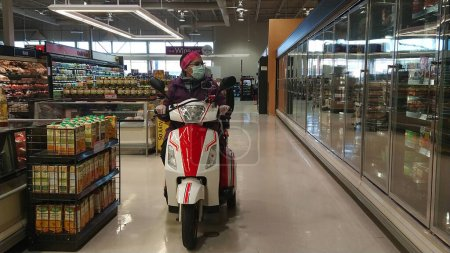 Photo for Toronto, Ontario, Canada - March 27, 2020 : Disabled woman on the mobility scooter in the medical mask and gloves shopping in empty grocery store during coronavirus pandemic outbreak. Mobile. - Royalty Free Image