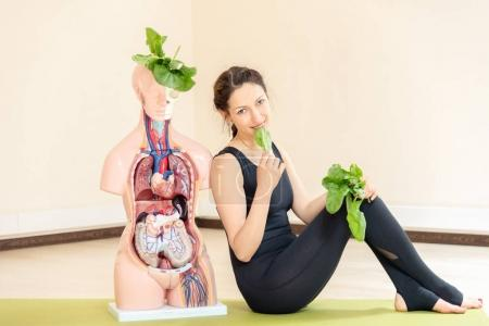 A yoga coach sits next to a medical dummy