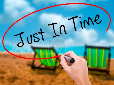 Photo for Man Hand writing Just In Time with black marker on visual screen. Isolated on sunbed on the beach. Business, technology, internet concept. Stock Photo - Royalty Free Image