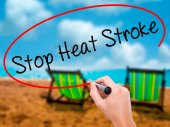 Man Hand writing Stop Heat Stroke with black marker on visual sc