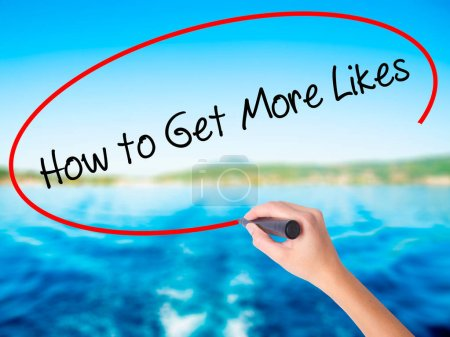 Woman Hand Writing How to Get More Likes? with a marker over tra