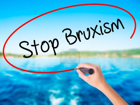 Woman Hand Writing Stop Bruxism with a marker over transparent b