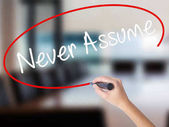 Woman Hand Writing Never Assume with a marker over transparent b