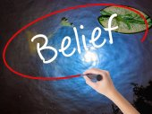 Woman Hand Writing Belief with marker over transparent board
