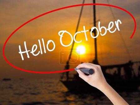 Photo pour Femme écriture à la main Bonjour Octobre avec un marqueur sur planche transparente. Isolé sur Sunset Boat. Concept d'entreprise. Photo de stock - image libre de droit