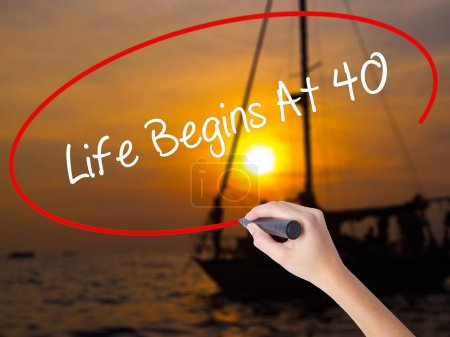 Woman Hand Writing Life Begins At 40  with a marker over transpa